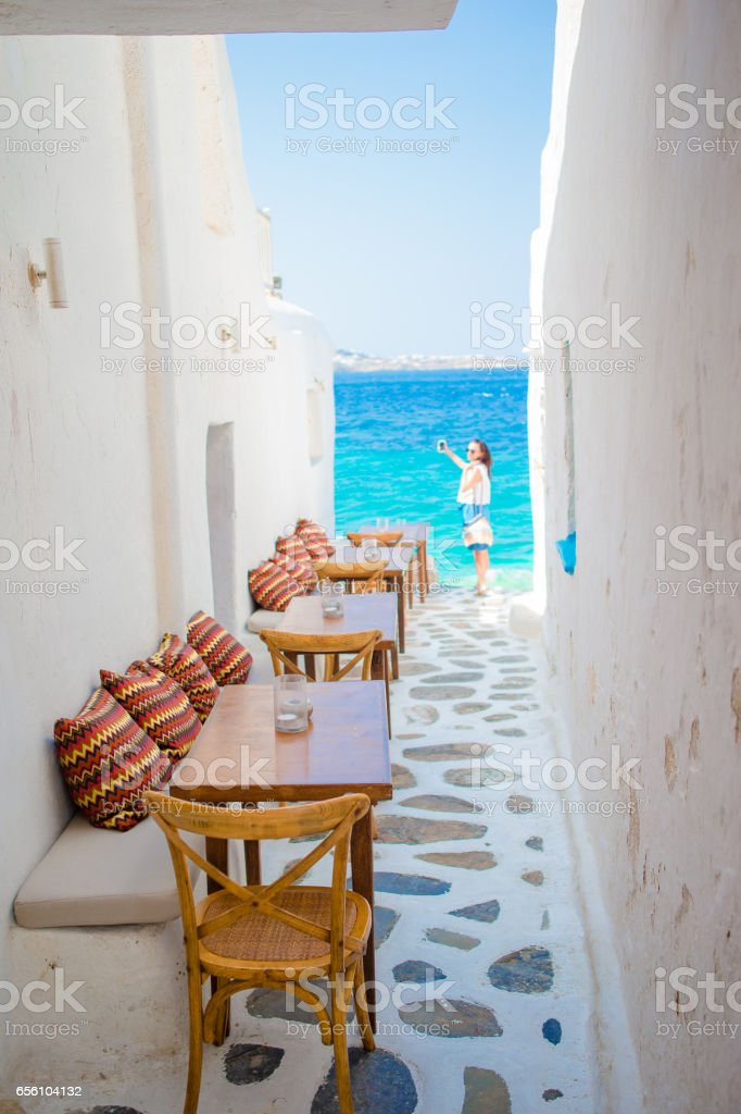 Benches with pillows in a typical greek outdoor cafe in Mykonos with amazing sea view on Cyclades islands stock photo