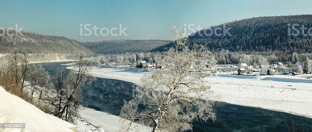 Bend in the winter river on the background of mountains stock photo
