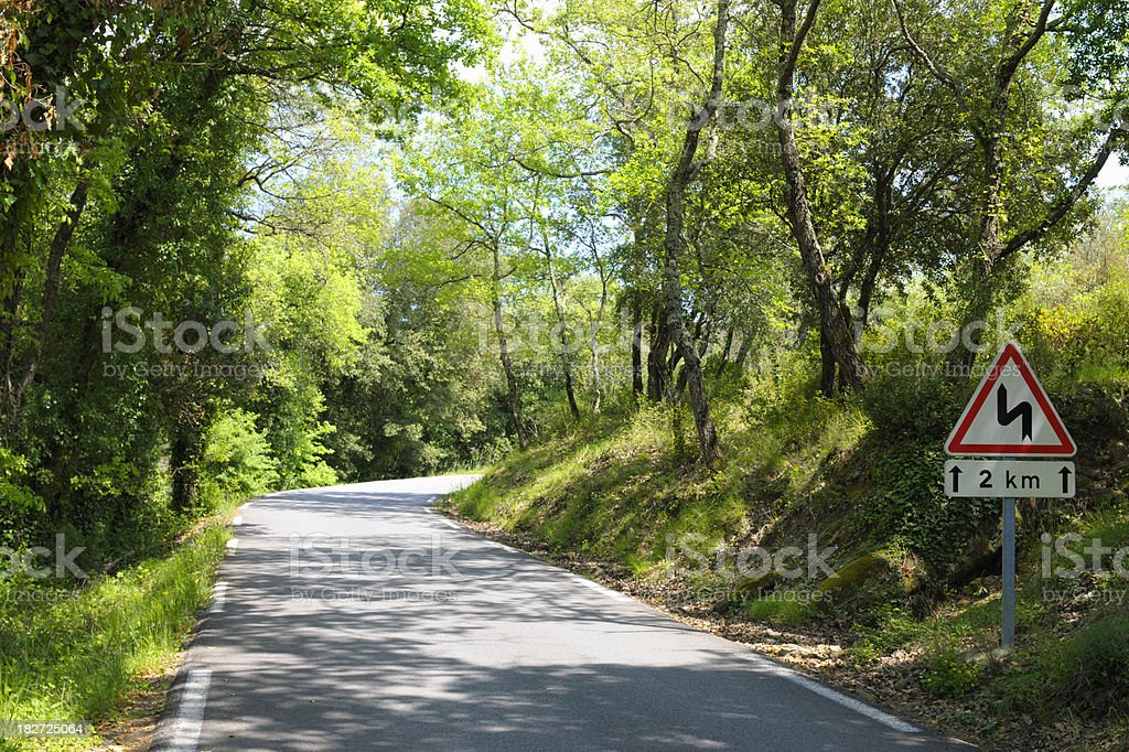 Bend on Country Road in France through Green Wood stock photo