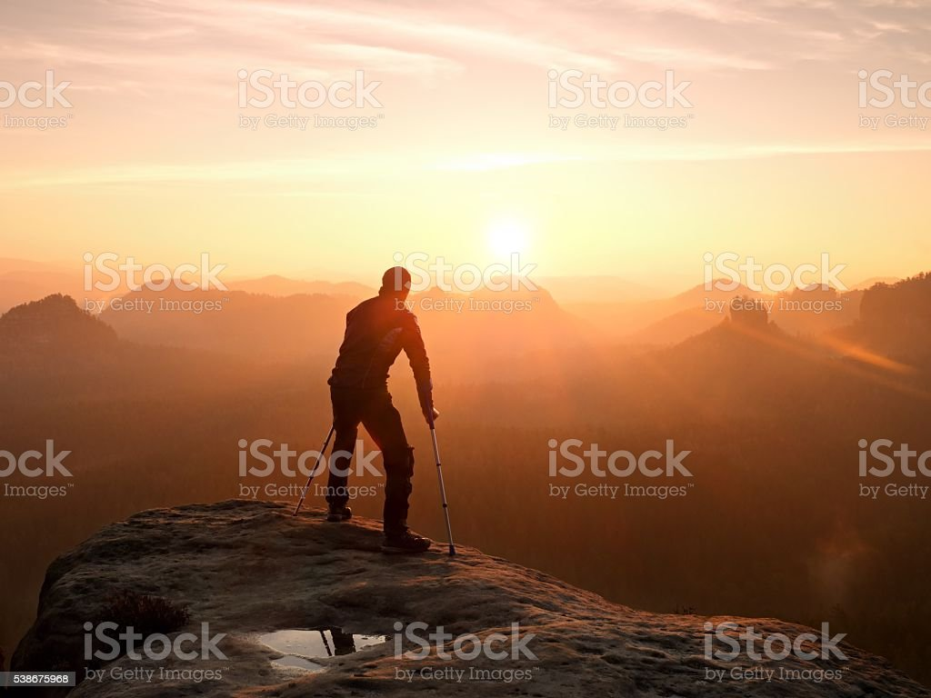 Bended man with medicine crutch.  Hiker with leg in immobilizer stock photo