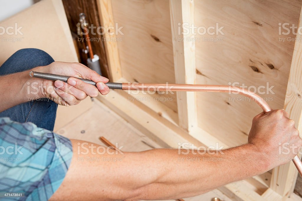 Bending Copper Pipe with a Spring stock photo