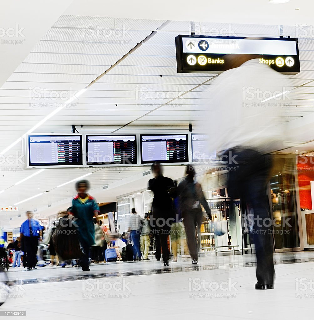 Beneath arrival/departure boards, people hurry through an airport royalty-free stock photo