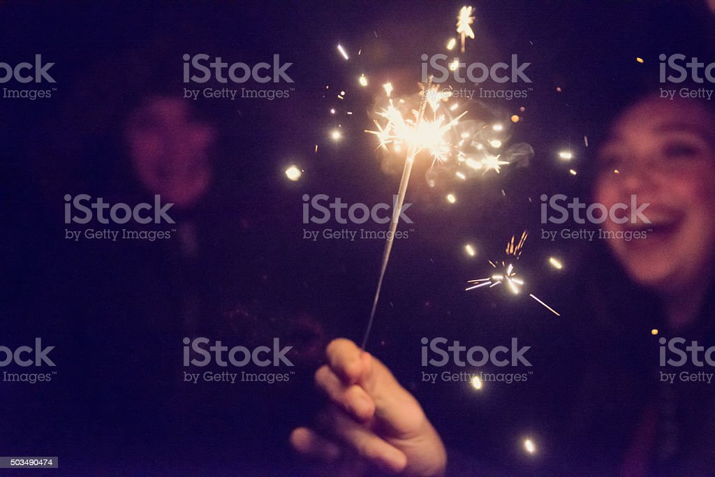 Bengal fire sparkling in front of woman outdoors at night. stock photo
