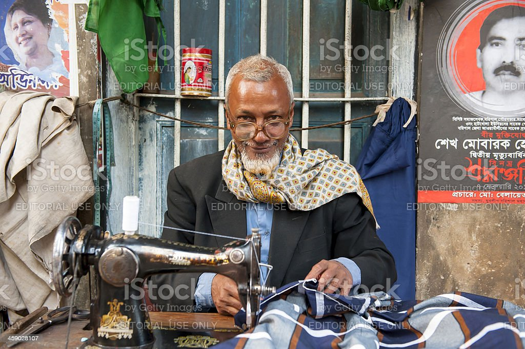 Bengali man behind sewing machine looking at camera stock photo