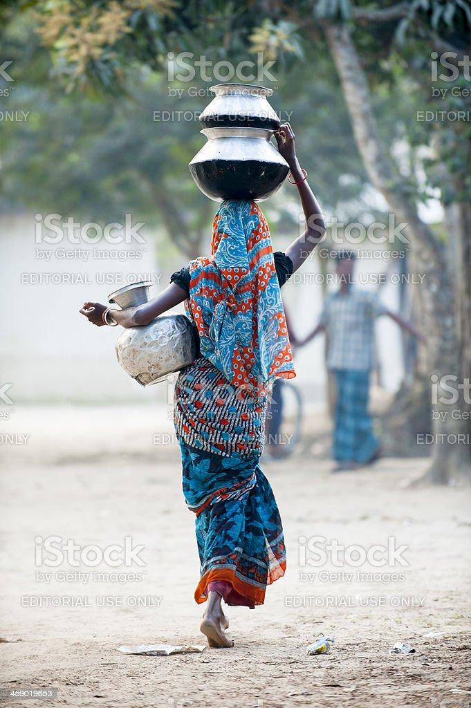Bengali woman heading water jar in village royalty-free stock photo