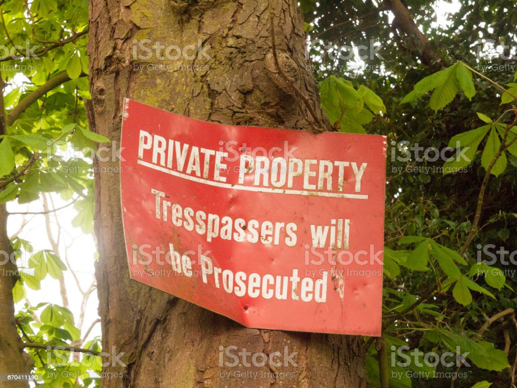 A Bent And Dinted Red Sign Attached to A Tree Saying Private Property Tresspassers will be Prosecuted stock photo