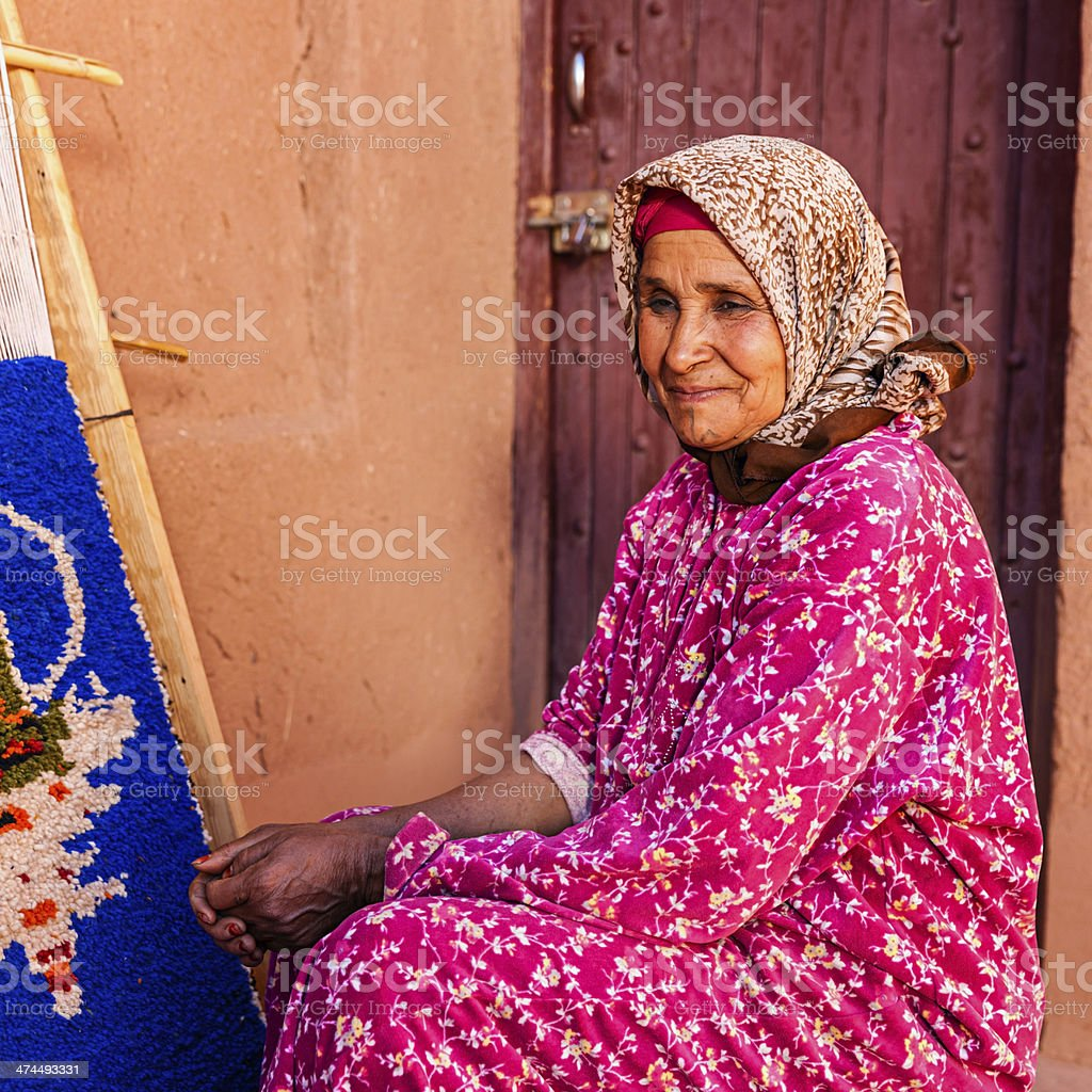 Berber woman weaving textiles, Ouarzazate, Morocco stock photo