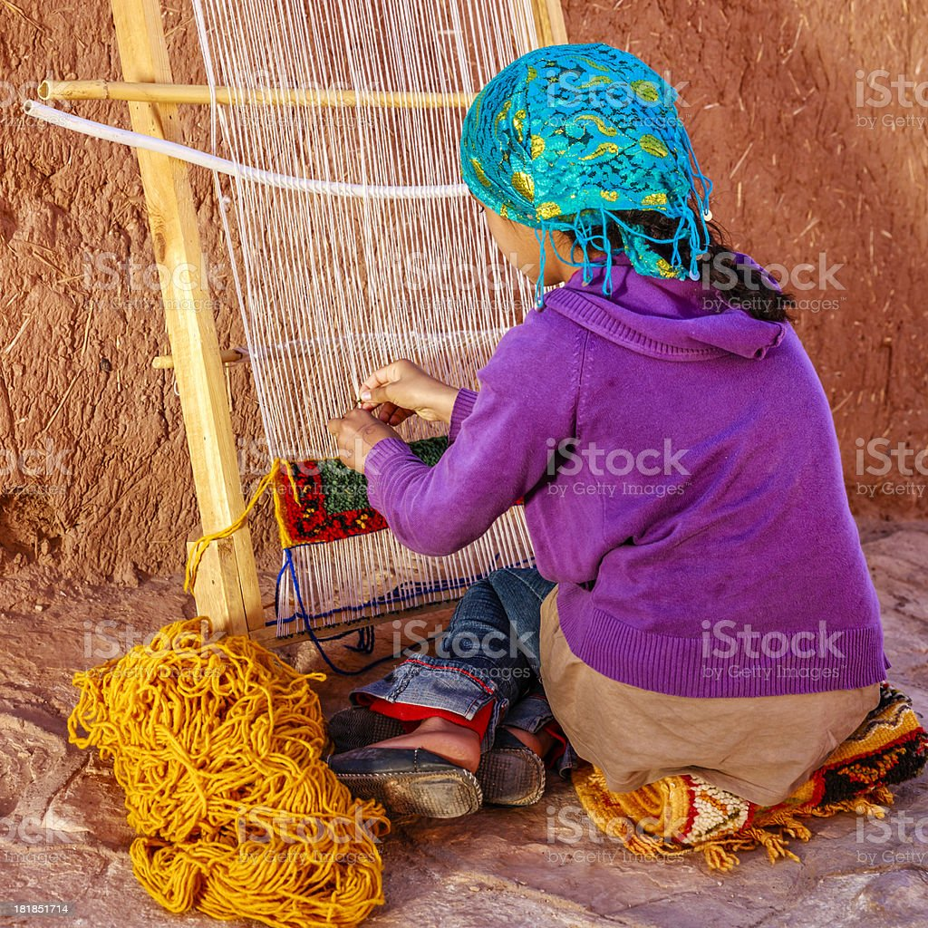 Berber young girl weaving textiles, Ouarzazate, Morocco stock photo