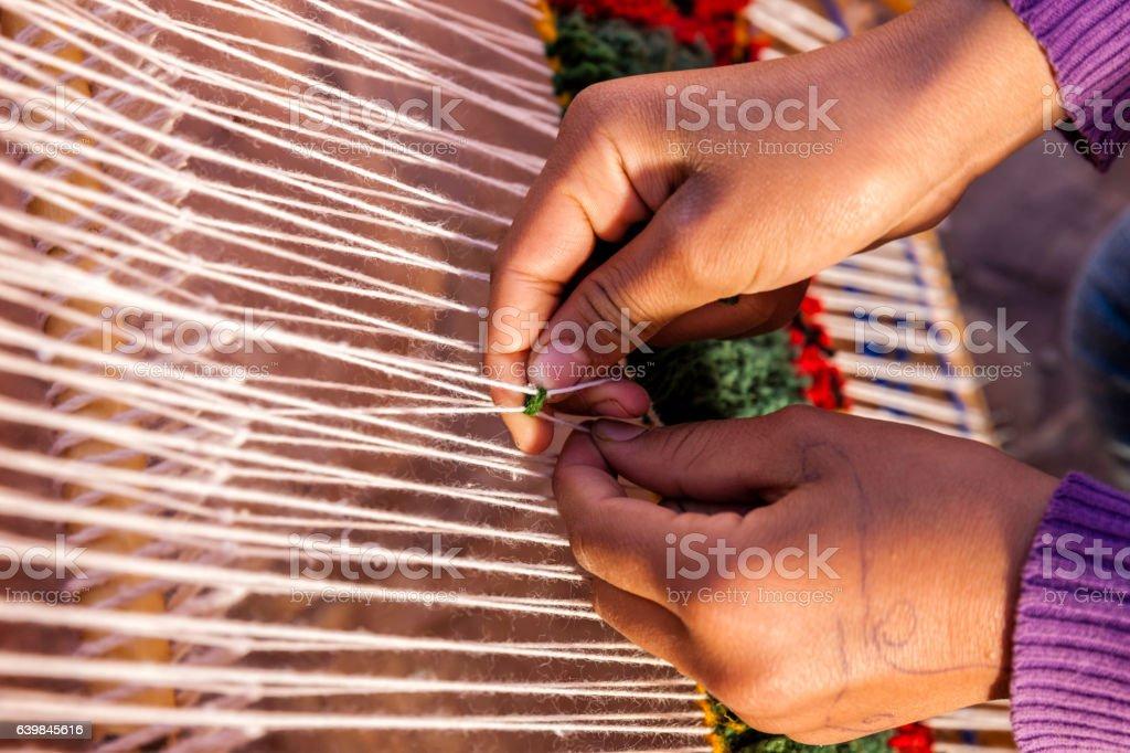 Berber young girl weaving textiles, Ouarzazate, Morocco stock photo