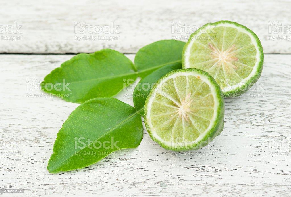 Bergamot fruit with green leafs on white wood background stock photo