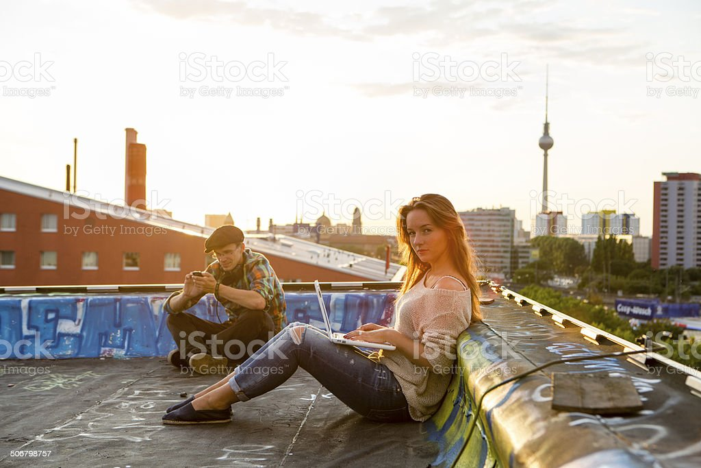 Berlin: young adults sitting on a roof, back lit stock photo