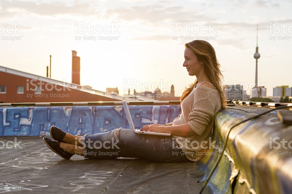 Berlin: young woman works at her laptop on a roof stock photo