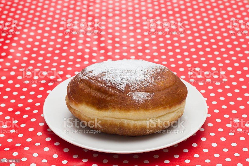 Berliner doughnut on white plate powdered with sugar stock photo