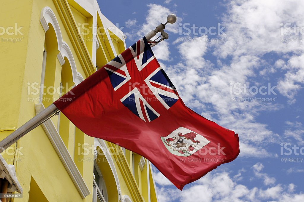 Bermuda flag hanged out on a yellow building  stock photo