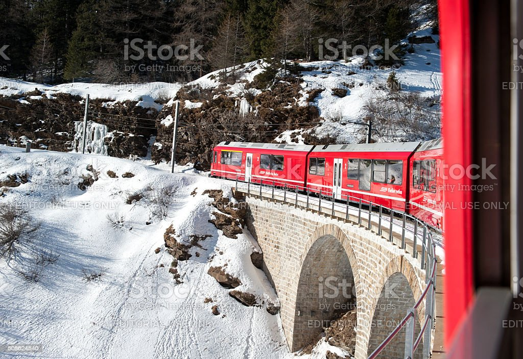 Bernina red train climbing in the snow, view from window stock photo