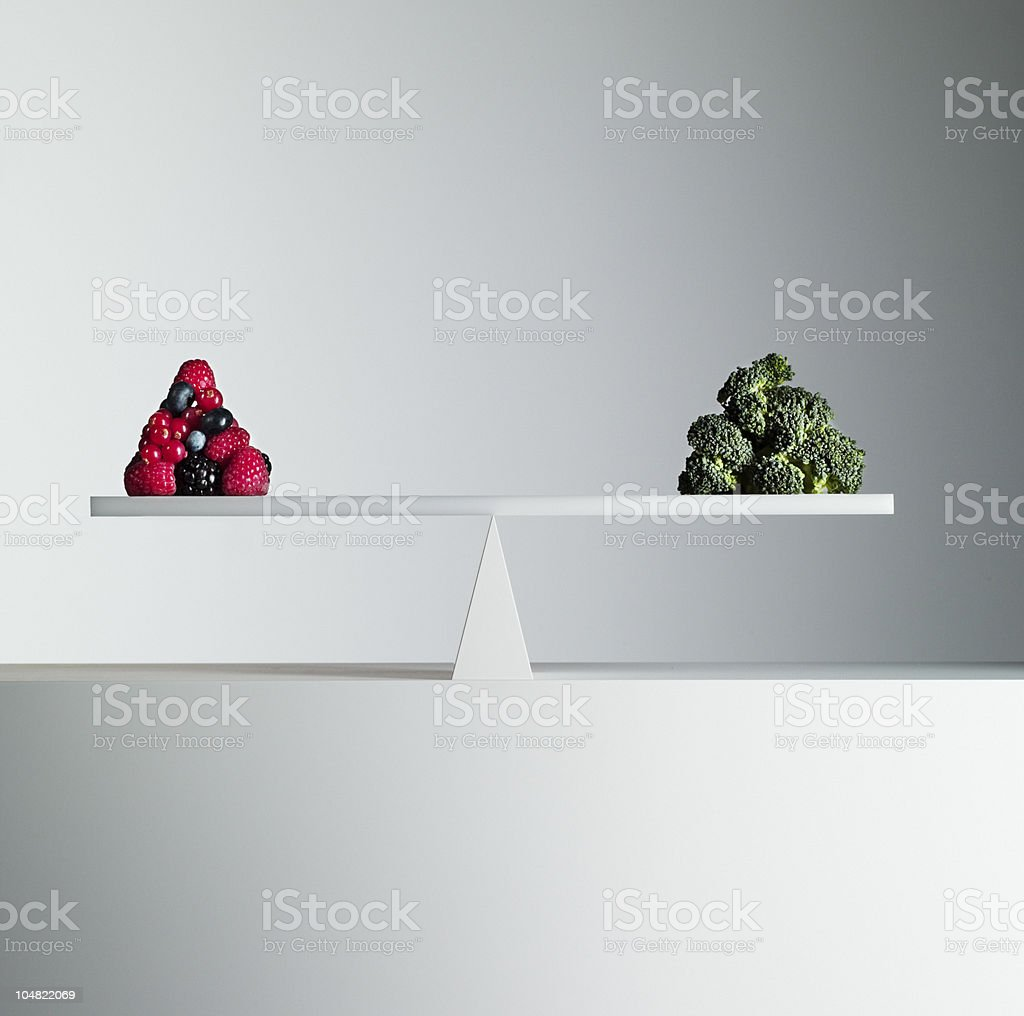 Berries and broccoli balanced on opposite ends of seesaw stock photo