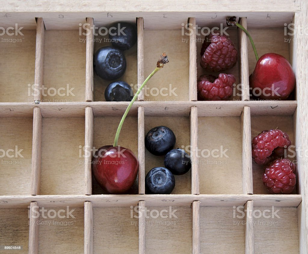berries and cherries in compartments stock photo