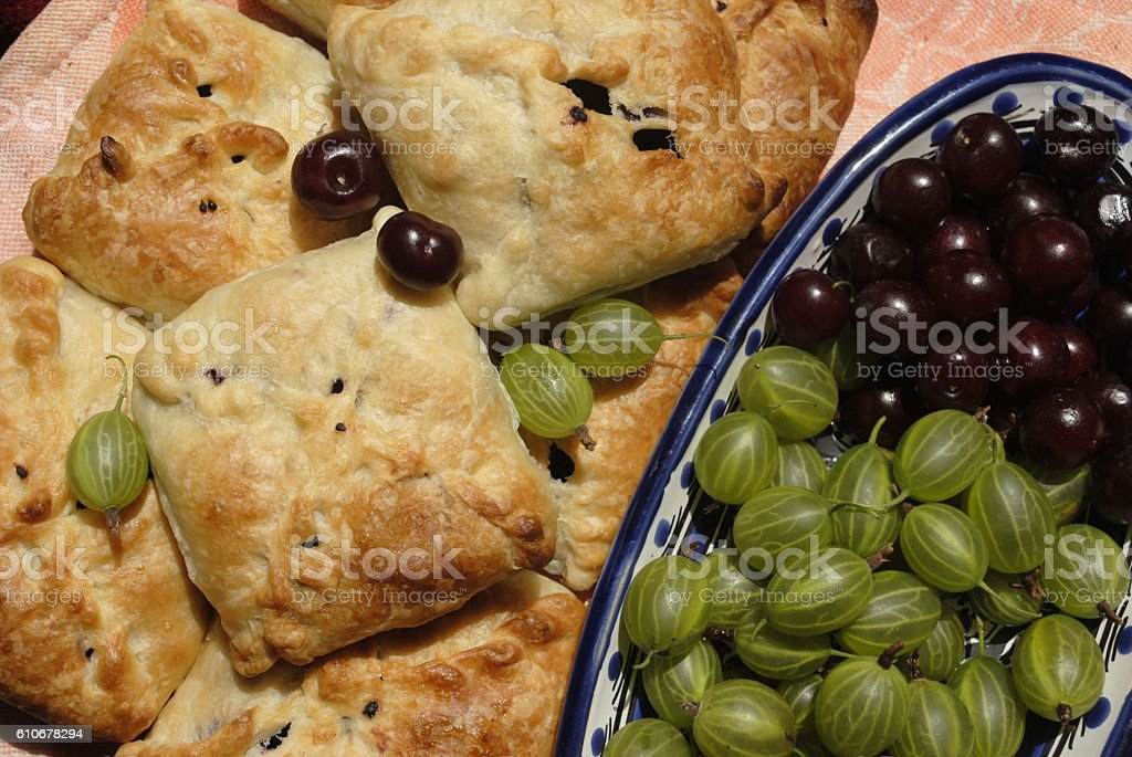 berries, cherries and gooseberries on the plate and cakes stock photo