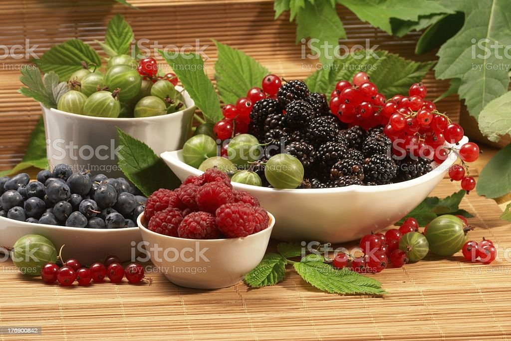 Berries in plates, on a table, among green leaves royalty-free stock photo