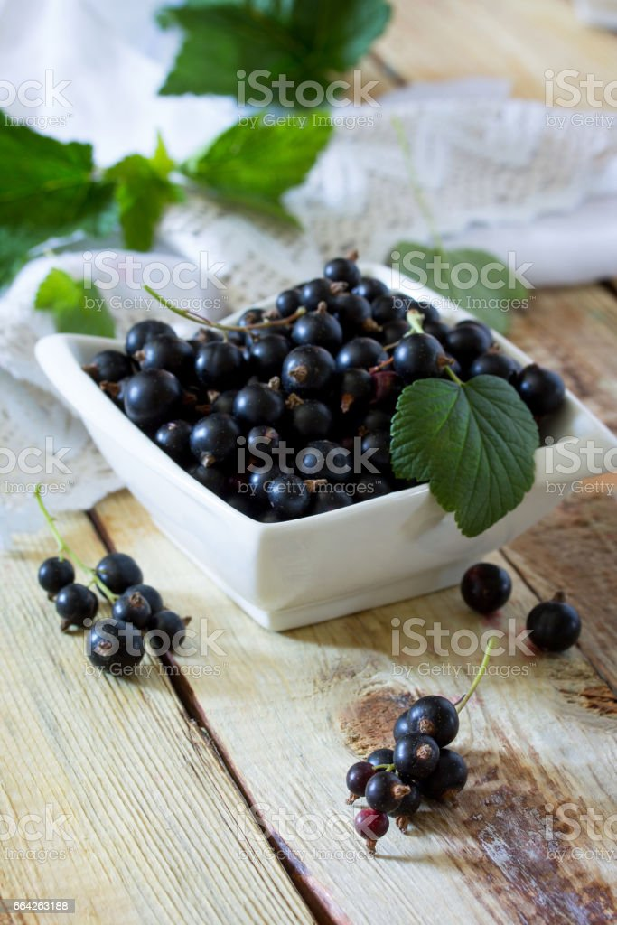 Berries of black currant on a wooden background. The concept of a healthy diet and diet. stock photo