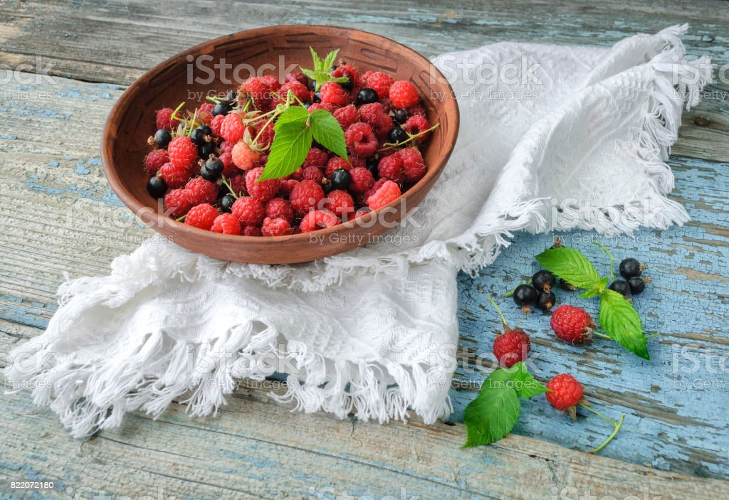 Berries of raspberries and currants in a plate on a wooden table stock photo