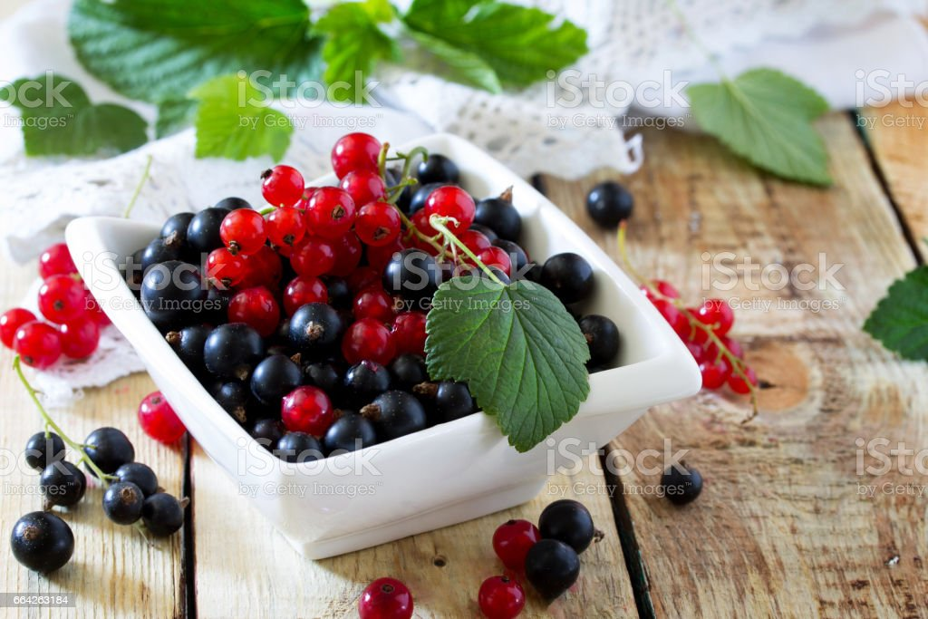 Berries of red and black currant on a wooden background. The concept of a healthy diet and diet. stock photo