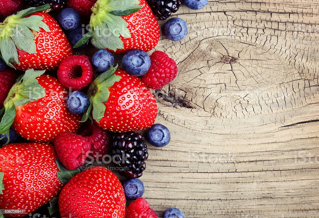 Berries on Wooden Background. Strawberries, Blueberry, Raspberries stock photo