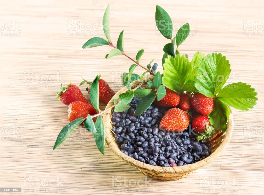 Berries red ripe strawberry, and blue honeysuckle far East in a wicker basket on the table stock photo