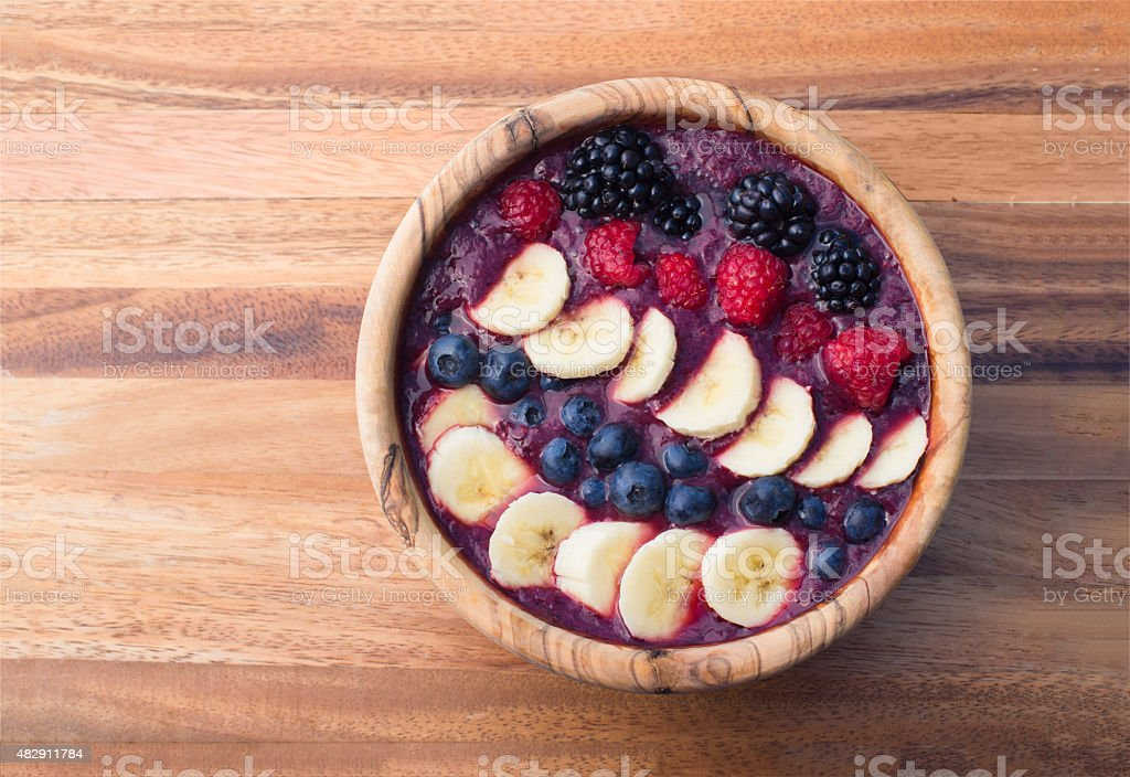 berry acai smoothie bowl with bananas, blueberries, raspberries and blackberries stock photo