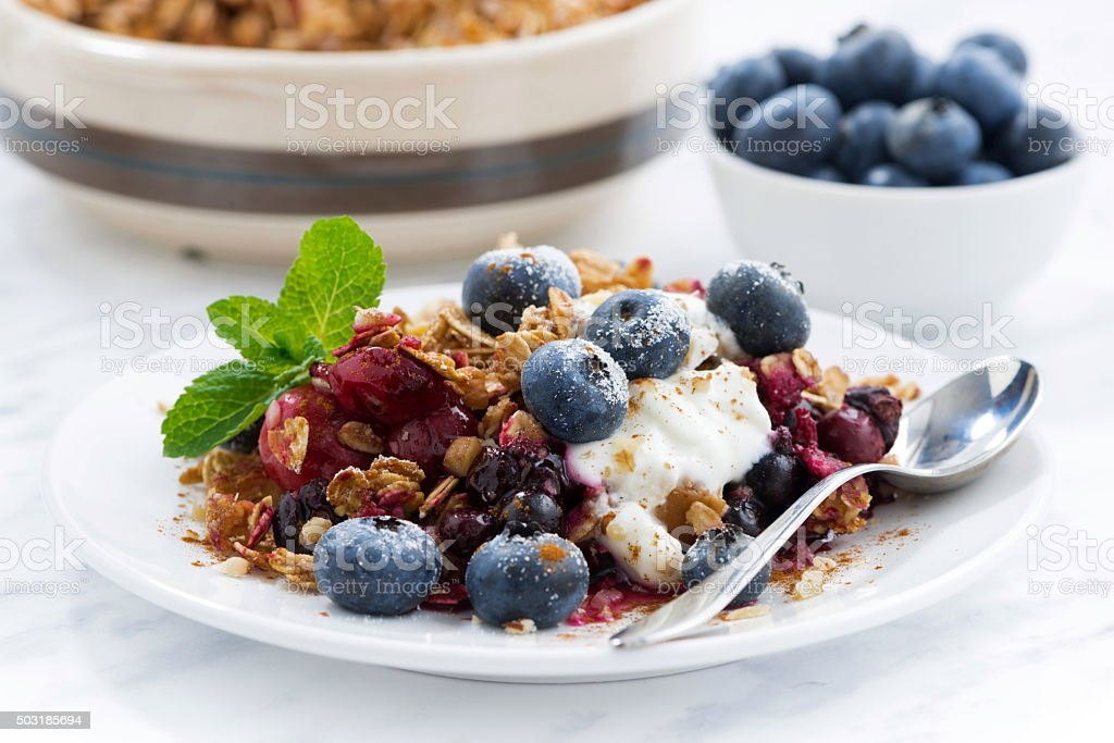 berry crumble with oat flakes and blueberries for breakfast stock photo