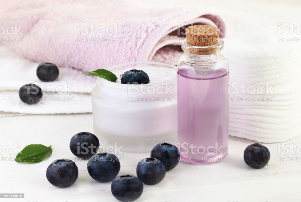 Berry extract cosmetic products. Lilac facial gel in glass bottle with blueberries stock photo