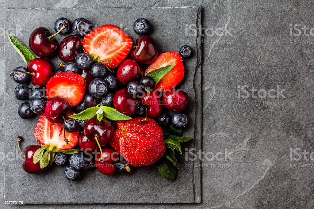 Berry mix - strawberries, cherries, blueberry on stone slate background stock photo