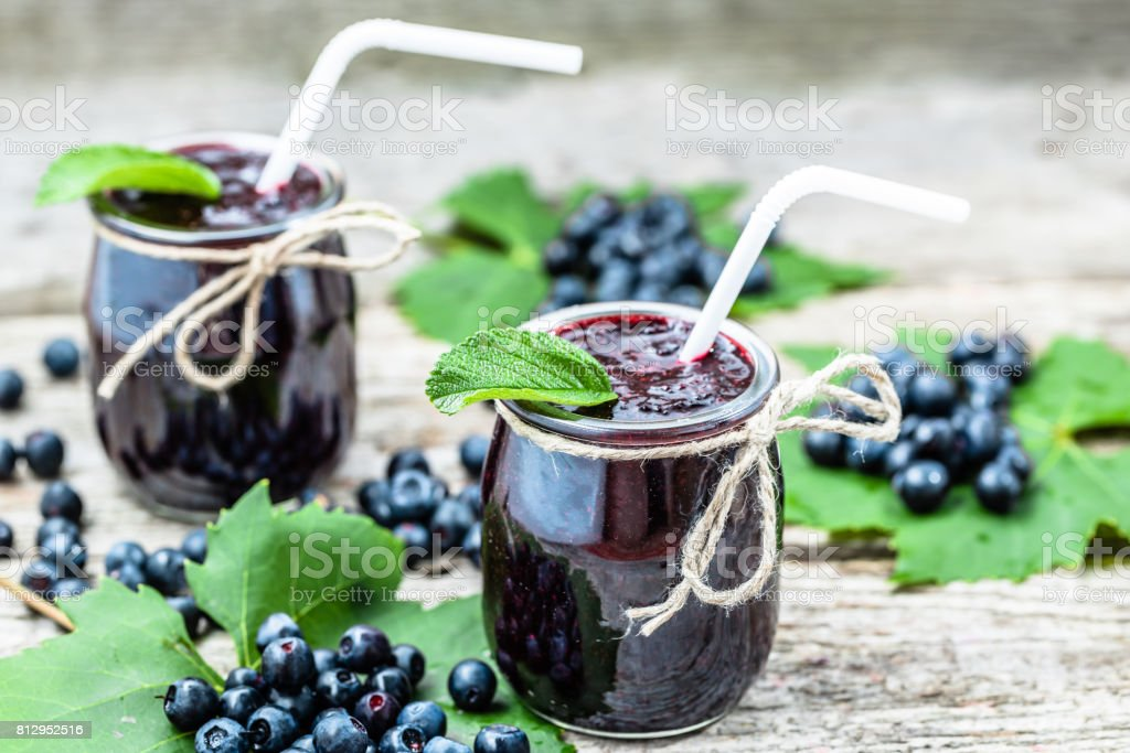 Berry smoothie in jar and fresh blueberry fruits stock photo