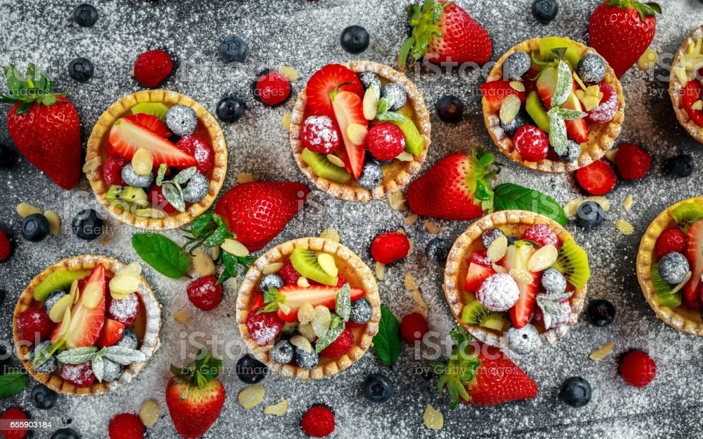 Berry tartlets with blueberries, raspberries, kiwi, strawberries, almond flakes in icing sugar. stock photo