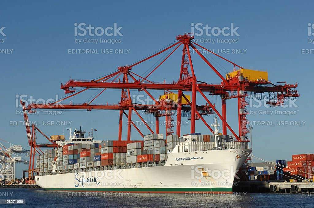 Berthed cargo ship being unoaded in a harbour. stock photo
