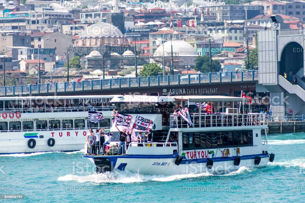 Besiktas football fans are travelling to match with boat at golden horn near karakoy istanbul stock photo