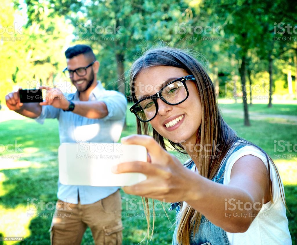 Bespectacled Couple Doing a Double Selfie in the Park stock photo