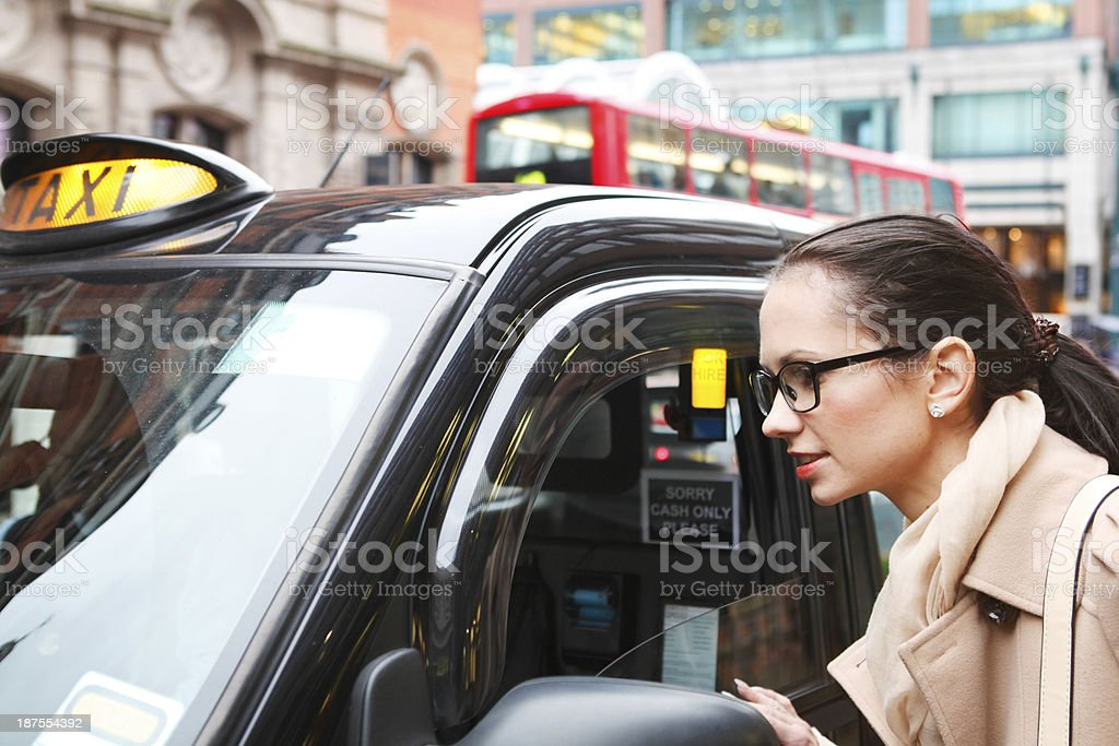 Bespectacled young girl ordering taxi in London stock photo