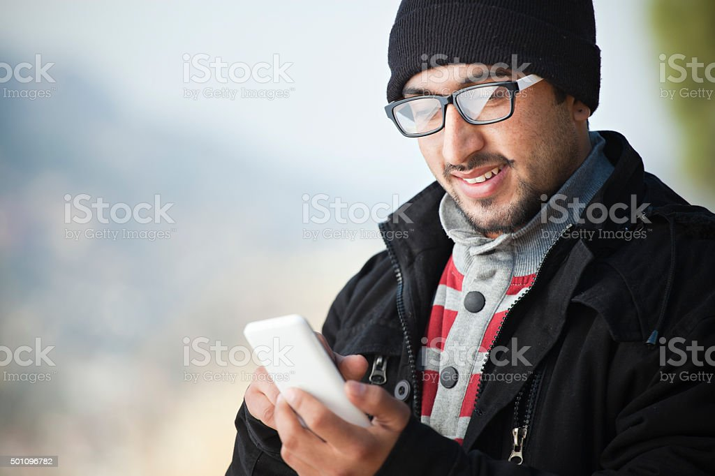 Bespectacled young man in winter dress using mobile phone. stock photo