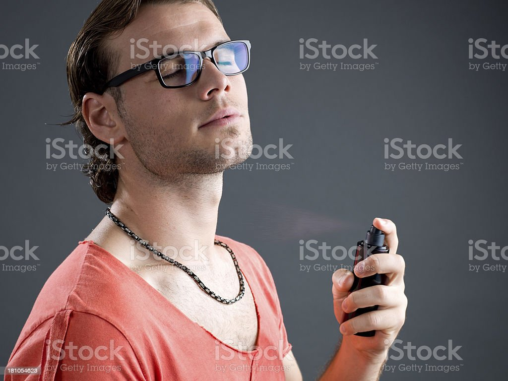 Bespectacled young man spraying perfume royalty-free stock photo