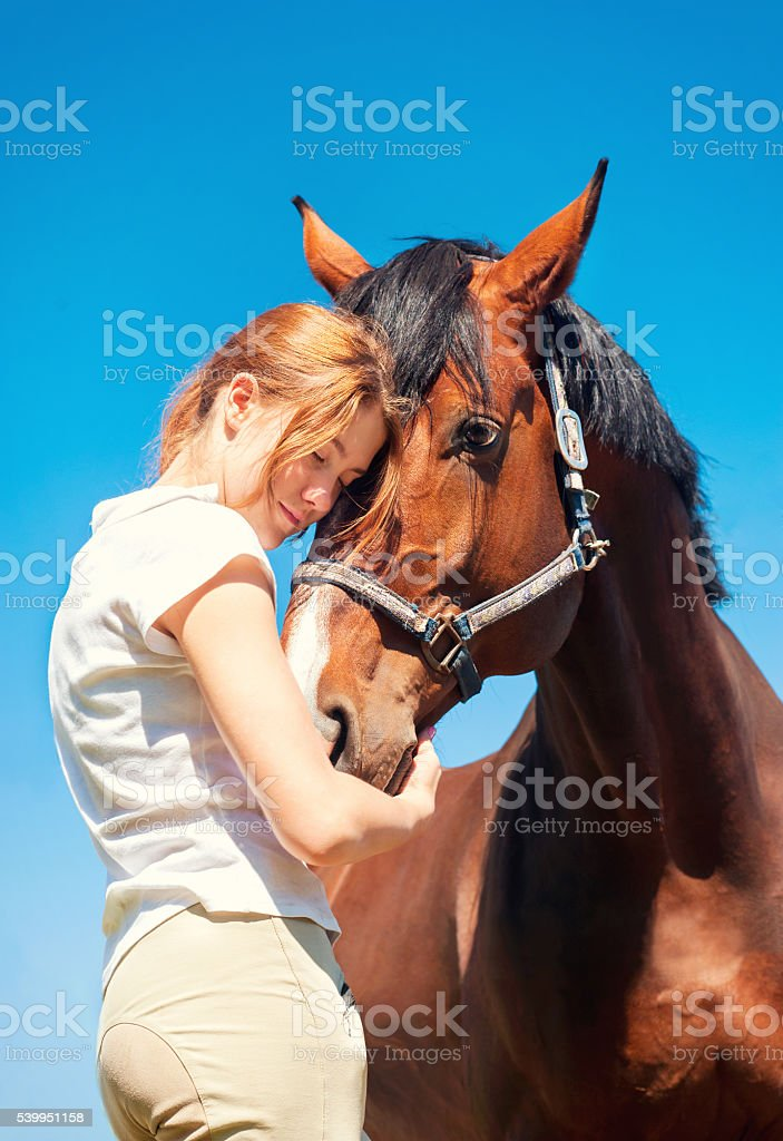 Best friend greeting. Redhead girl embracing horse. stock photo