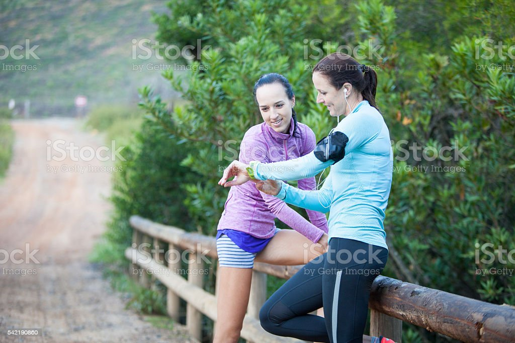 Best friends check out their running times stock photo
