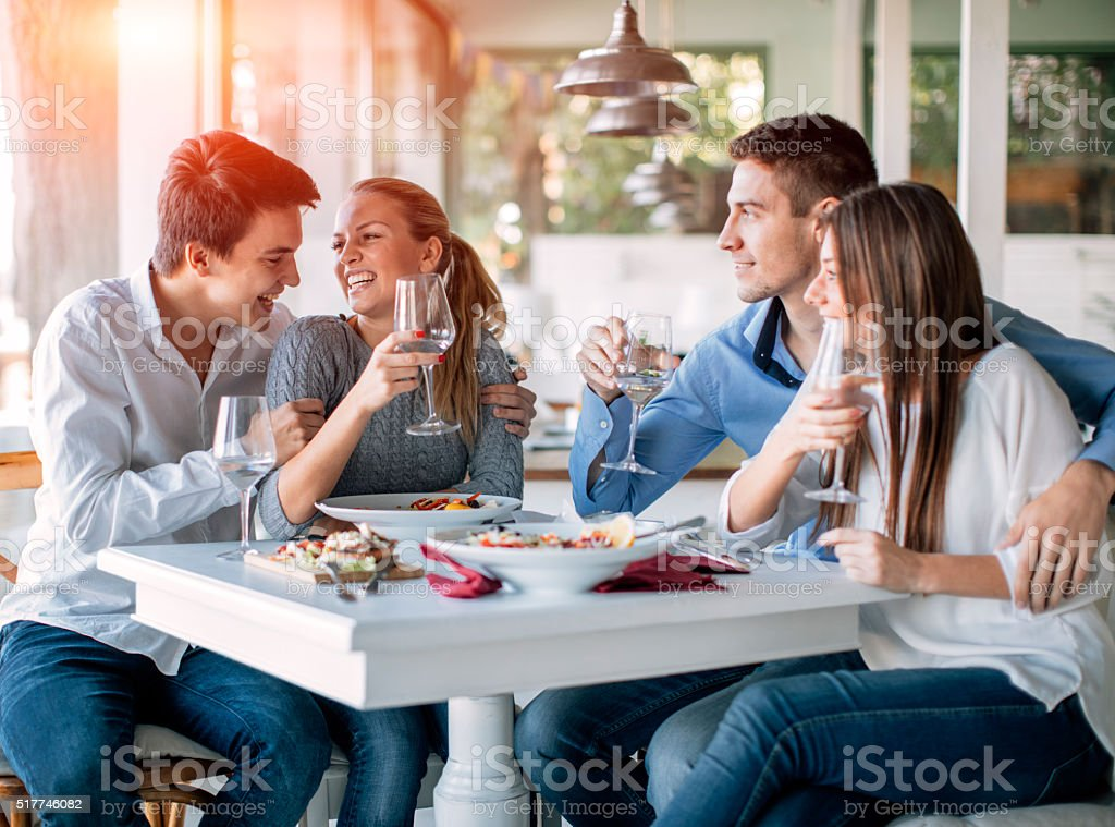 Best Friends Drinking And Eating In Restaurant. stock photo