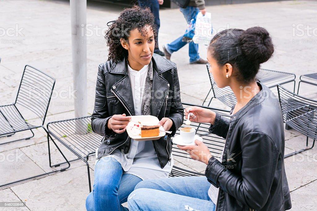 Best friends drinking coffee in city stock photo