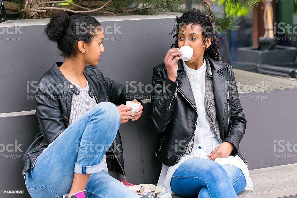 Best friends drinking coffee in city stock photo
