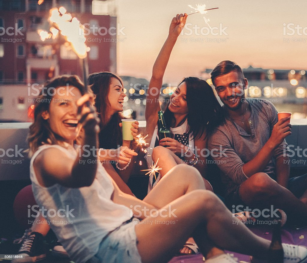 Best friends drinking on a rooftop party stock photo