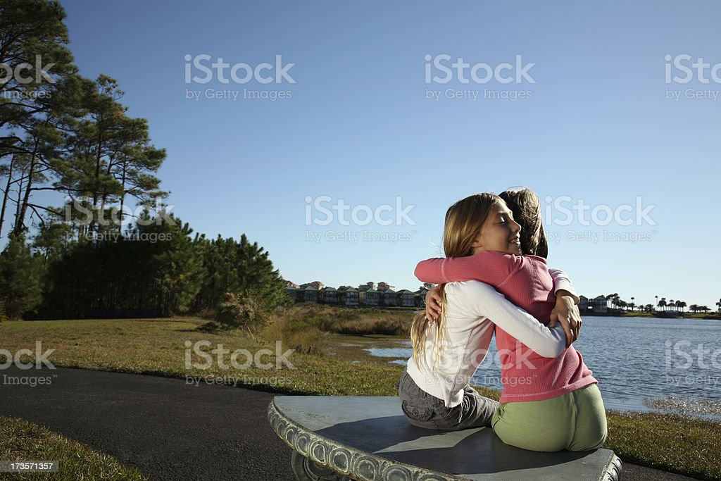 Best Friends Hugging sitting on Park Bench Lakeside royalty-free stock photo