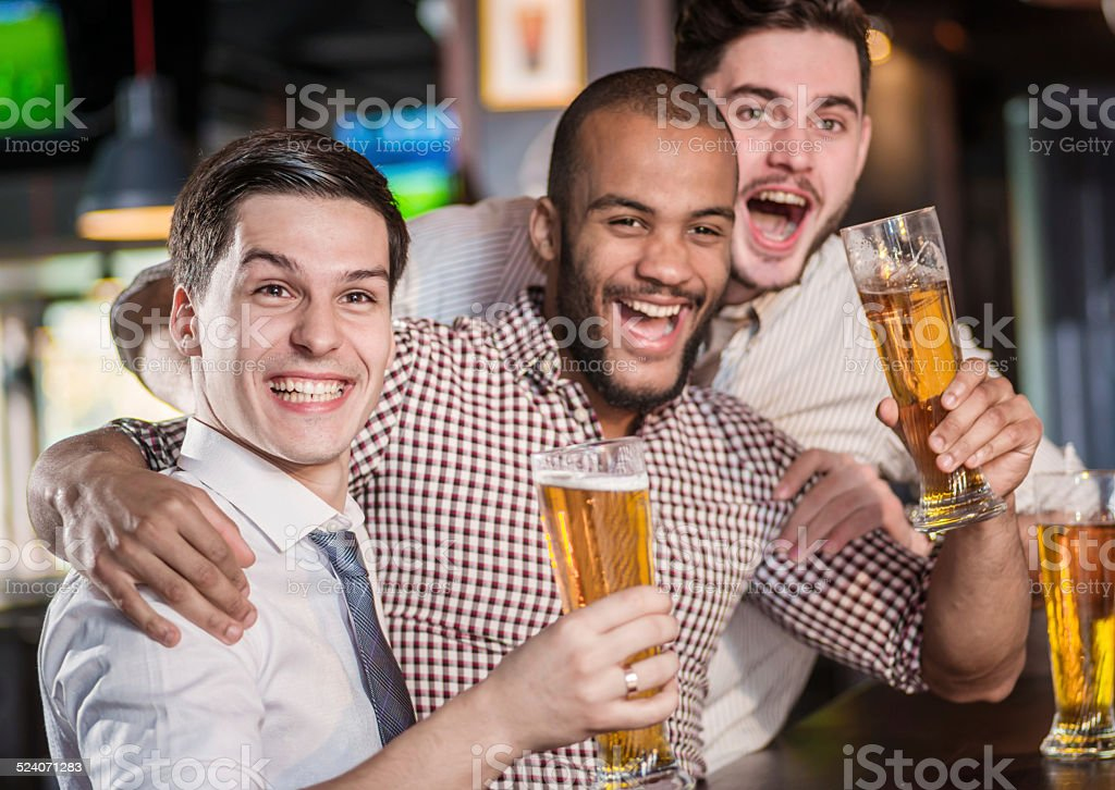 Best friends in a bar. Men shout and rejoice stock photo