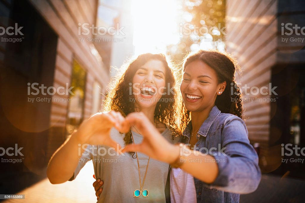 Best Friends Laugh Whilst Showing Heart With Hands stock photo