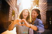 Best Friends Laugh Whilst Showing Heart With Hands